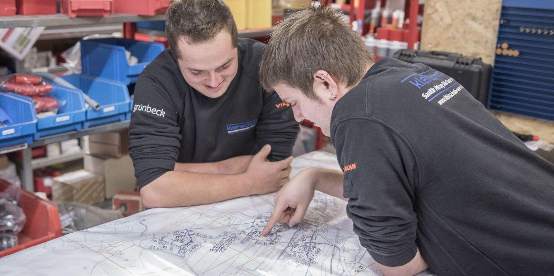 Simon Schlagbauer und Markus Mauracher, Mitarbeiter von Installationsbetrieb Timo Kleinschroth, Schleching, beugen sich über Pläne